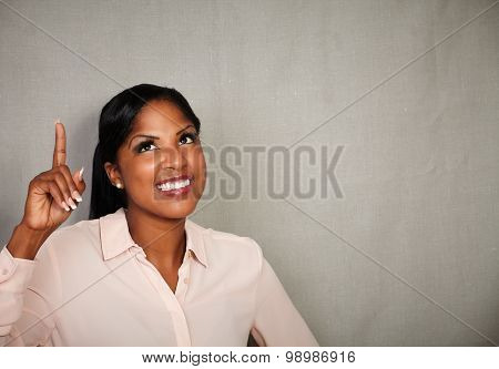 Young Businesswoman Pointing Up While Smiling