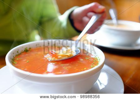 Bowl Of Hot Vegetable Soup And Hand Holding Spoon.