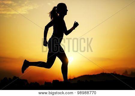 Silhouette Of Girl Running At Sunset.