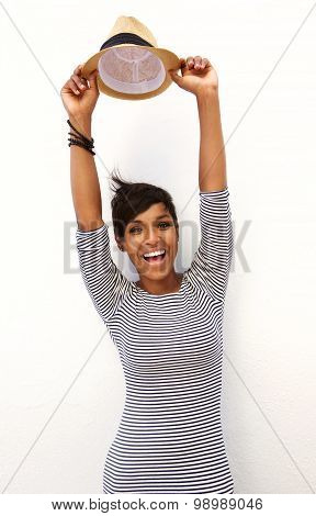 Smiling Young Woman With Arms Raised And Holding Hat