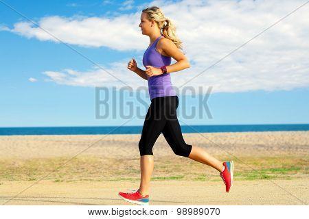 Young Woman Jogging Along Beach.