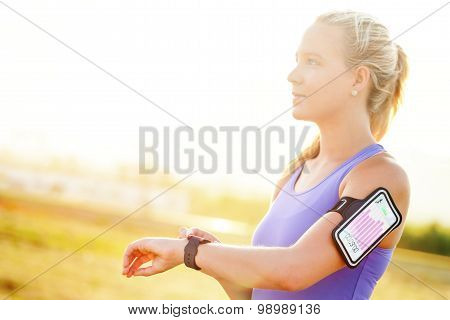 Young Woman Setting Workout On Smart Watch.