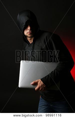 Hacker with computer and laptop on colorful dark background