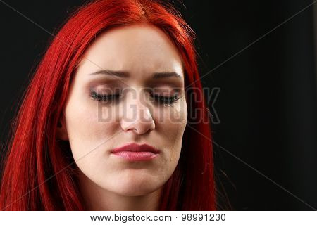 Face of young woman with tear drop on dark background