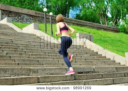 Young woman jogging at stairs outdoors