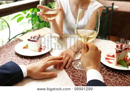 Hands of newlyweds holding glasses of wine at table in cafe, closeup