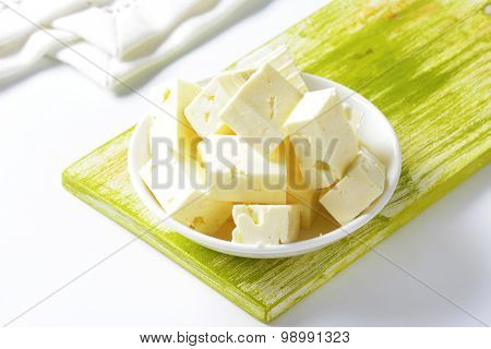 bowl of feta cheese cubes on green wooden cutting board