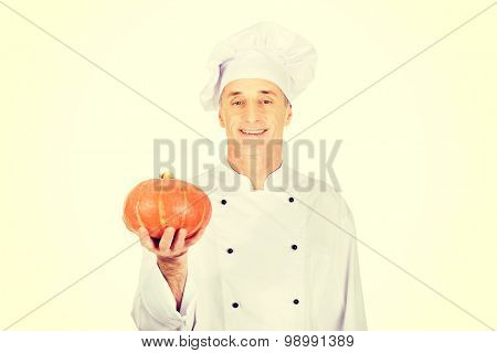 Male chef in uniform holding a pumpkin