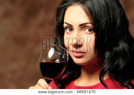 Pretty young woman with wineglass on brown background