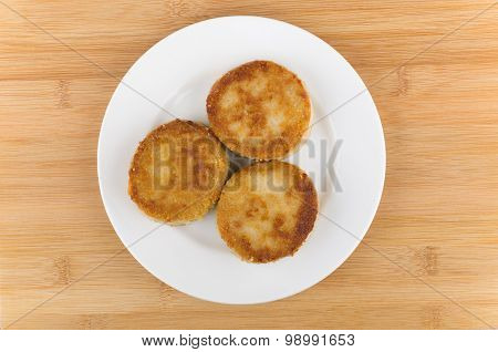 Three Fried Meatballs In White Plate Glass On Wooden Table