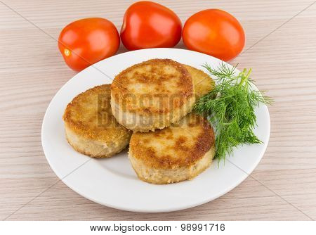 Fried Cutlets In Plate With Dill And Tomatoes On Table