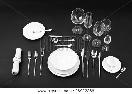 Table setting, close up, on black background