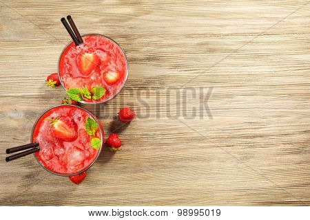 Glasses of strawberry smoothie with berries on table close up