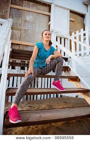 Woman Runner Sitting On Wooden Steps Of A Beach Hut
