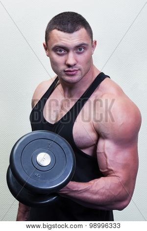 bodybuilder with a dumbbell on a background of a wall