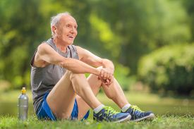 foto of sportswear  - Athletic senior in sportswear sitting on grass in a park and listening to music on headphones - JPG