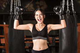 foto of boxing  - Cheerful woman in boxing gloves celebrating victory - JPG