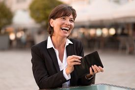 picture of vivacious  - Laughing vivacious attractive woman sitting at an outdoor urban restaurant making a payment reaching inside her wallet for money or a credit card - JPG
