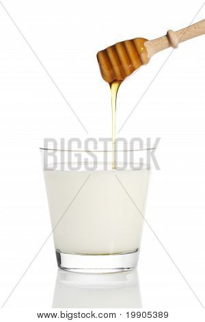 honey falling from a honey dipper in a jar with milk
