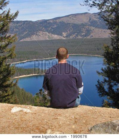 Hombre se sienta en el mirador en un parque frente a un lago