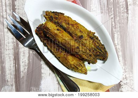 Stuffed Karela or stuffed Bitter gourd shallow frying in a pan
