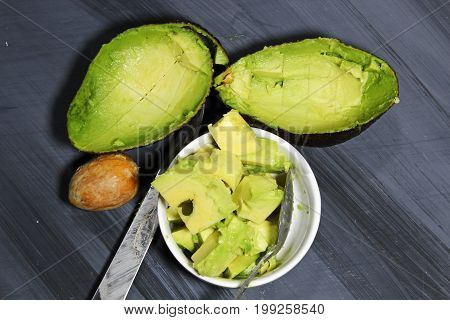 Chopped Avocado in a bowl on wooden background