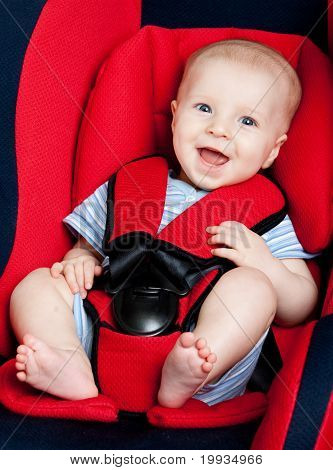 Happy boy in car armchair
