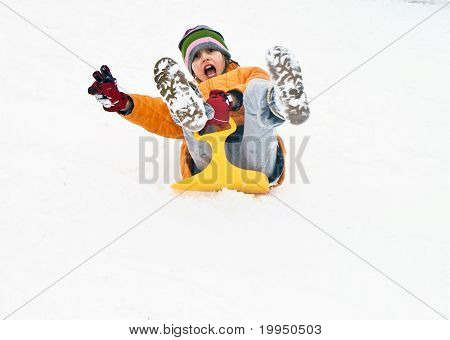 girl sledging down the hill in wintertime
