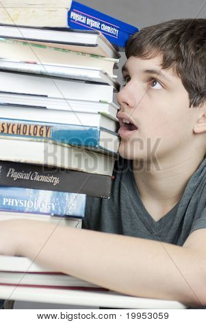 Overwhelmed Teen Looks Up At Stack Of Textbooks