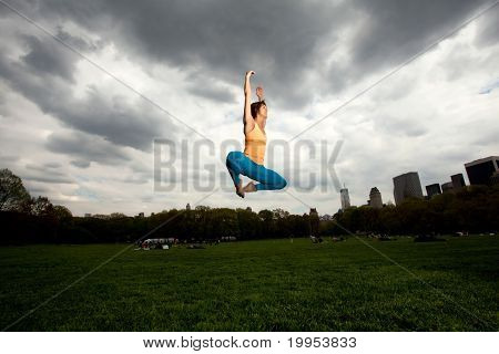 Young Pretty Woman In Yellow Top Doing Yoga And Exercising In Central Park