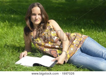 Young Girl Lying On The Grass With An Open Book
