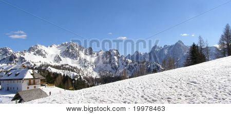 Alpine village and snowy mountains panorama