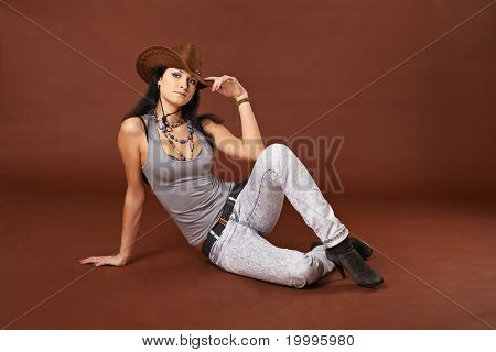 Girl In Cowboy Hat Sitting On A Brown