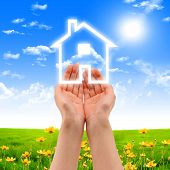 stock photo of business success  - human hands holding model of a house against nature background - JPG