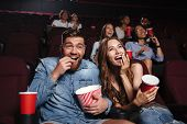 Happy couple eating popcorn and laughing while sitting and watching movie at the cinema poster