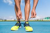 Runner tying running shoes laces on run tracks lanes in stadium getting ready for race competition o poster