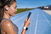 Running music motivation woman listening to phone app with headphones. Runner looking at smartphone  poster