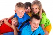 stock photo of happy kids  - A group of happy kids dressed in bright colors huddle together with smiles on their faces - JPG