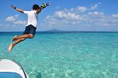 man jumps into the sea on his holiday