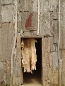 stock photo of longhouse  - An animal fur hangs in the doorway of the Wolf Clan Long House at an Iroquois settlement - JPG