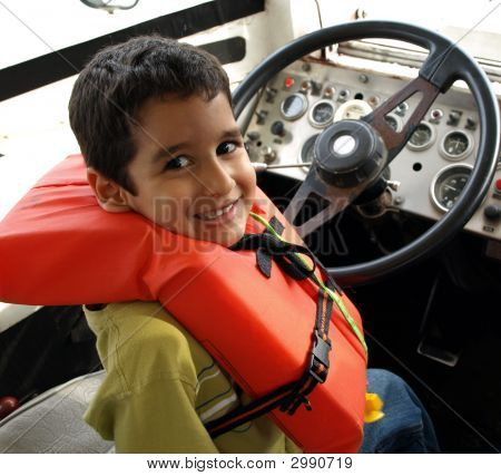 Little Boy Driving A Big Boat