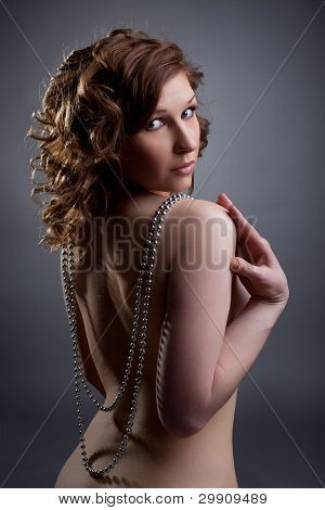 nude young woman posing with silver beads