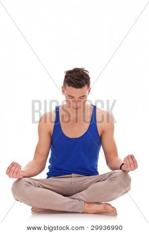 young handsome man meditating in lotus position. Relaxed, and focused on his inner peace