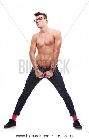sexy muscular man wearing glasses and no shirt holding his jeans on white background. full body picture of a suspicious shirtless man