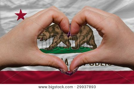 Over American State Flag Of California Showed Heart And Love Gesture Made By Hands