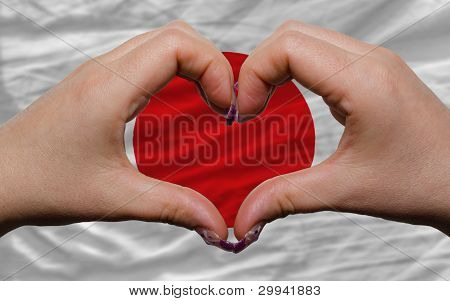 Over National Flag Of Japan Showed Heart And Love Gesture Made By Hands