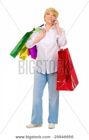 Senior woman with packets talking by mobile phone isolated