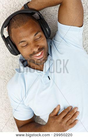 happy Man lying on Floor mit Kopfhörer, genießen Sie Musik mit geschlossenen Augen, lächelnd.?