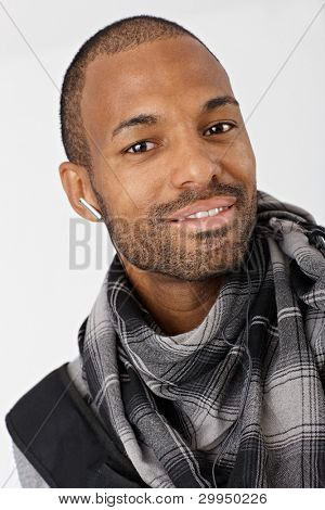 Closeup portrait of ethnic guy smiling wearing scarf and earbuds.?