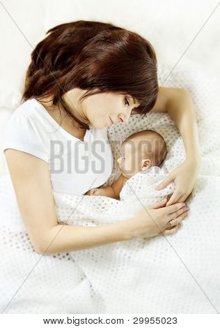Mother Embracing Sleeping Newborn Baby. Protection And Mother's Love Concept..